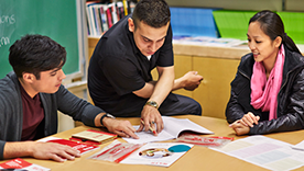 Group of people reading IELTS support materials