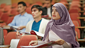 Young woman sitting in lecture theatre